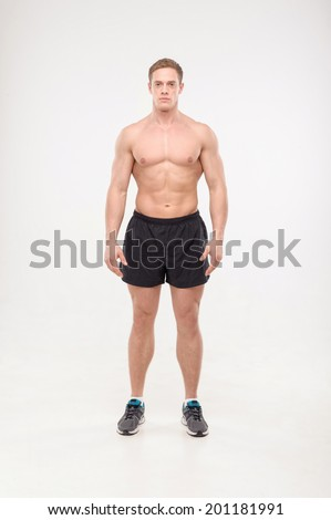 Shirtless healthy athletic young man standing isolated on white background - stock photo