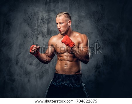 Shirtless kick boxer showing his punches and kicks over grey background in a studio.