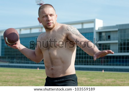 Shirtless male athlete winds up to throw an american football - stock photo