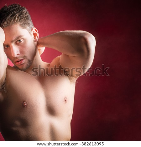 Shirtless male model against a red background - Athletic young male fitness model - stock photo