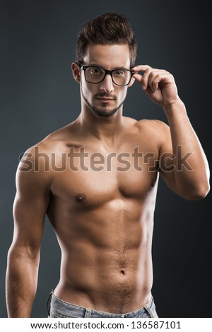 Shirtless male model posing with glasses over a blue background - stock photo