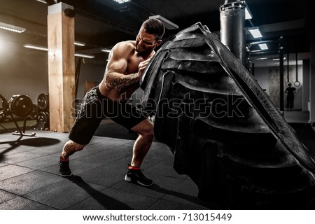 Shirtless man flipping heavy tire at gym
