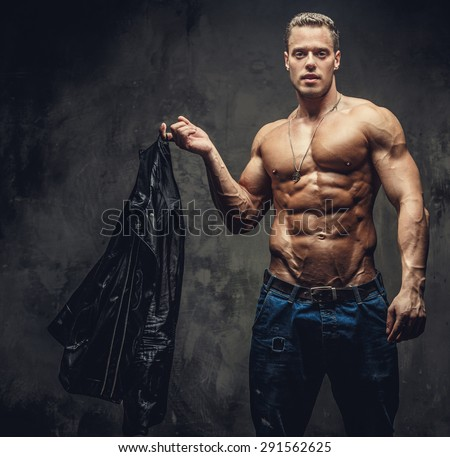 Shirtless man in blue jeans holding leather jacket. - stock photo