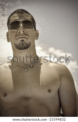 Shirtless man in sunglesses looking ahead. - stock photo