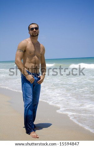 Shirtless man in sunglesses standing on a beach - stock photo