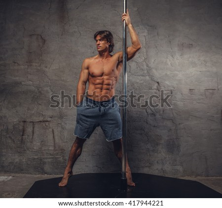 Shirtless man pole dancing on a grey background.