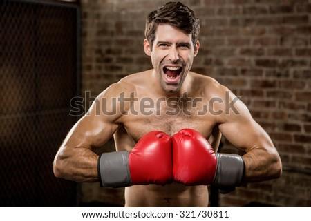 Shirtless man smiling while wearing boxing gloves at the gym - stock photo
