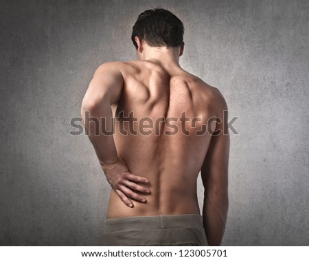 Shirtless man touching his back for the pain - stock photo