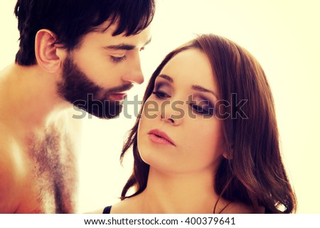 Shirtless man whispering to woman's ear.