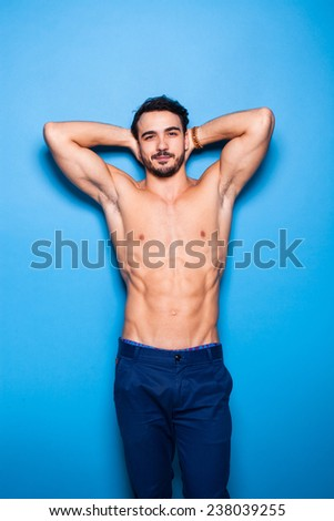 shirtless man with beard having his hands on nape, on blue background - stock photo