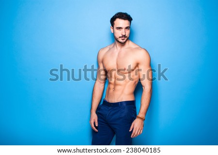 shirtless man with beard on blue background - stock photo