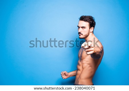 shirtless man with beard on blue background, pointing the camera and threatening with his fist - stock photo