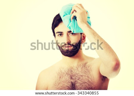 Shirtless man with headache and ice bag on his head. - stock photo