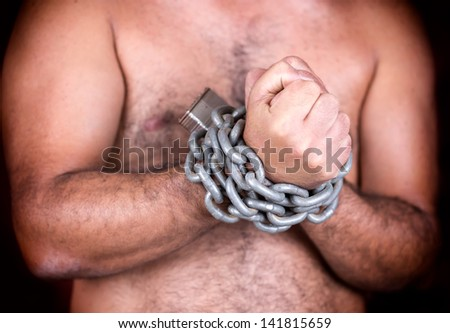 Shirtless man with his hands chained with strong steel chains and a padlock (on a black background) - stock photo