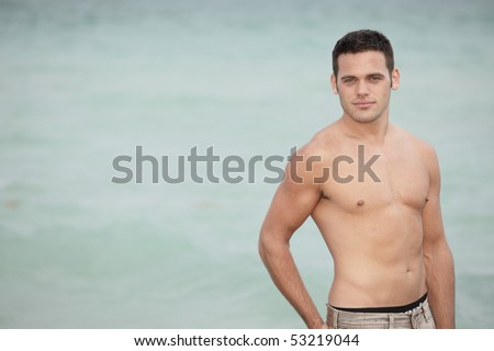 Shirtless man with water in the background