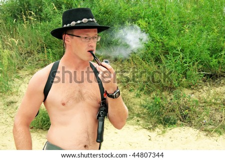 shirtless men with the revolver in a holster and hat smoke a pipe - stock photo