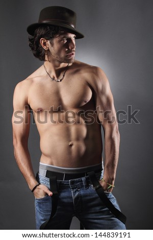 Shirtless model poses with hat and suspenders . Grey backdrop - stock photo