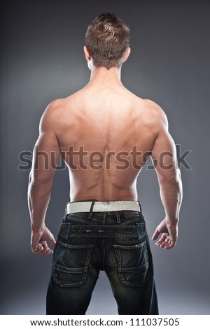 Shirtless muscled fitness man showing his back. Cool looking. Tough guy. Blue eyes. Blond short hair. Wearing black sunglasses. Tanned skin. Studio shot isolated on grey background. - stock photo