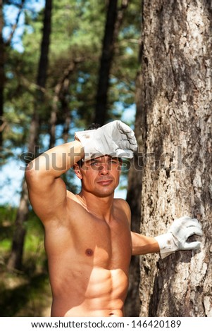 Shirtless muscled fitness man with working gloves in forest. Resting and staring.