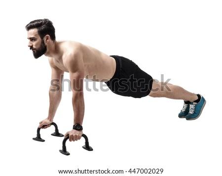 Shirtless muscular athlete doing push-up on push up bars. Full body length portrait isolated over white studio background. - stock photo