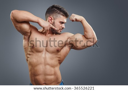 Shirtless muscular athletic man pointing to his strained biceps muscle. Sexy bodybuilder showing his muscular body on grey background with copy space. - stock photo