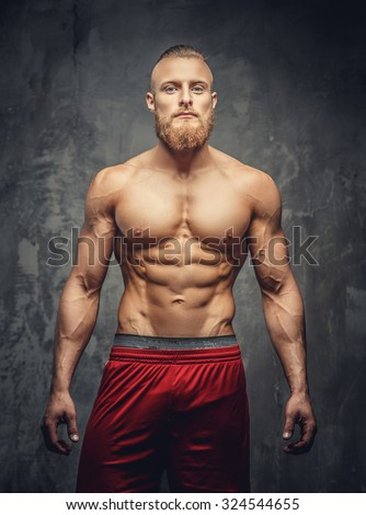 Shirtless muscular bearded man in red pants posing in studio over grey background. - stock photo