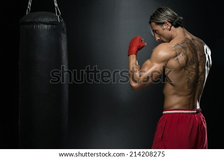 Shirtless Muscular Boxer With Punching Bag In Gym - A Man With A Tattoo In Red Boxing Gloves - Boxing On Black Background - The Concept Of A Healthy Lifestyle - The Idea For The Film About Boxing - stock photo
