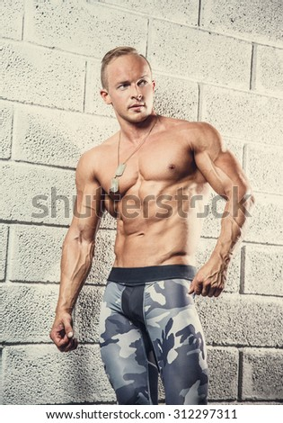 Shirtless muscular caucasian man in army pants posing over grey wall.
