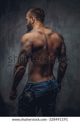 Shirtless muscular guy from back in blue jeans with tattooed hands.