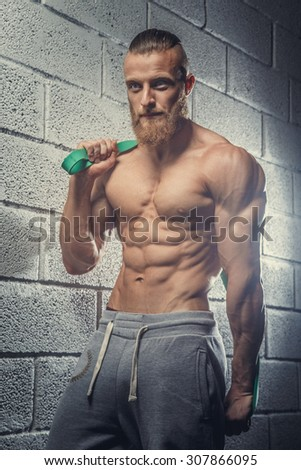 Shirtless muscular guy with beard doing exercises in a gym.