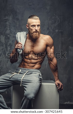 Shirtless muscular guy with beard in grey pants posing on grey box in studio.
