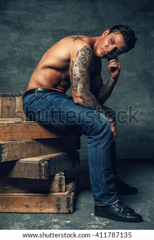 Shirtless muscular guy with tattoo on arm dressed in blue jeans.