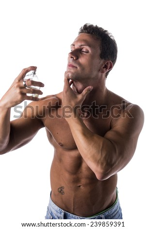 Shirtless muscular male model spraying cologne on white background, eyes closed - stock photo