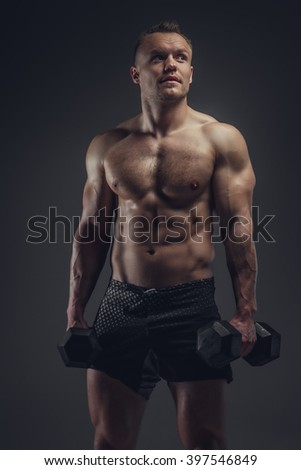 Shirtless muscular man holds a pair of dumbbels.