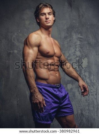 Shirtless muscular man in a blue shorts posing against a grey wall.