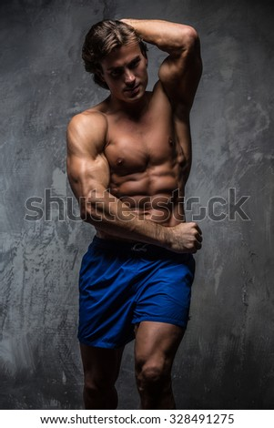 Shirtless muscular man in blue shorts posing over grey background.