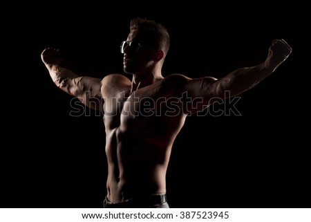 shirtless muscular man in pants and sunglasses posing in studio