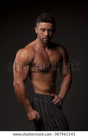 shirtless muscular man in pants posing in studio