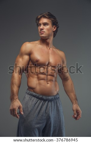 Shirtless muscular man isolated on a grey background.