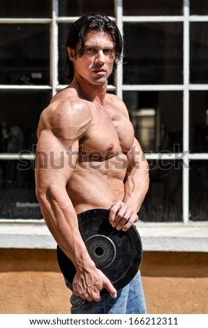 Shirtless muscular man ouidoors holding weight disc, looking at camera - stock photo