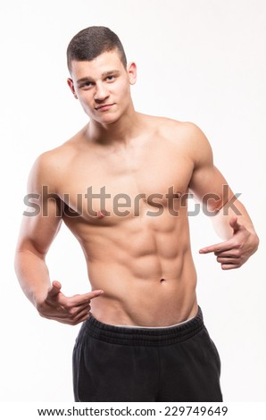Shirtless muscular man pointing his six pack - studio shoot  - stock photo
