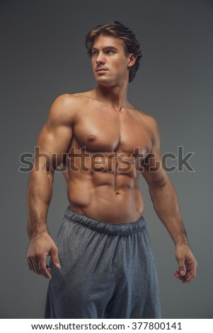 Shirtless muscular man posing against the grey wall.