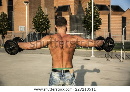 Shirtless Muscular Man Seen from the Back Lifting Weights Outdoor. Showing Healthy Body - stock photo