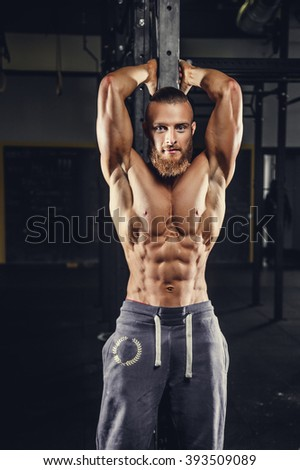 Shirtless muscular man with beard in a grey sports pants.