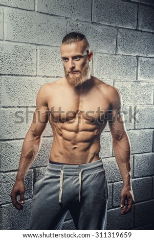 Shirtless muscular man with beard in grey pants posing over wall from grey bricks.