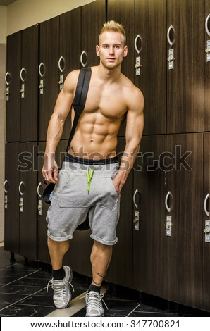 Shirtless muscular young male athlete in gym dressing room, with backpack on shoulder - stock photo