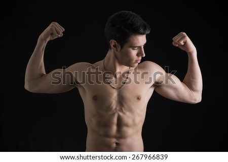 Shirtless muscular young man doing double biceps pose, isolated on black background - stock photo