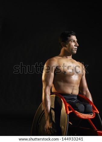 Shirtless paraplegic cycler against black background - stock photo
