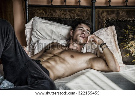 Shirtless sexy male model lying alone on his bed in his bedroom, looking away with a seductive attitude - stock photo