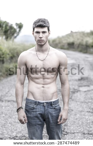 Shirtless sexy muscular young man in jeans walking along rural road  - stock photo
